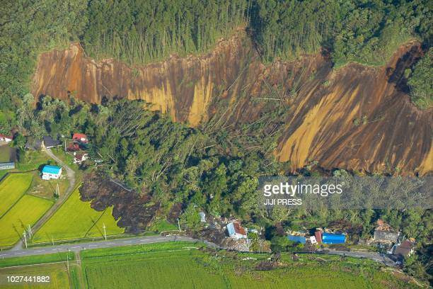 This picture shows an aerial view of houses damaged by a landslide in Atsuma town Hokkaido prefecture on September 6 after an earthquake hit the...