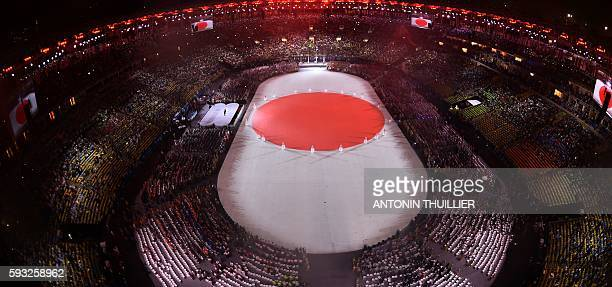 TOPSHOT This picture shows an overview of the presentation of Tokyo 2020 during the closing ceremony of the Rio 2016 Olympic Games under the rain at...
