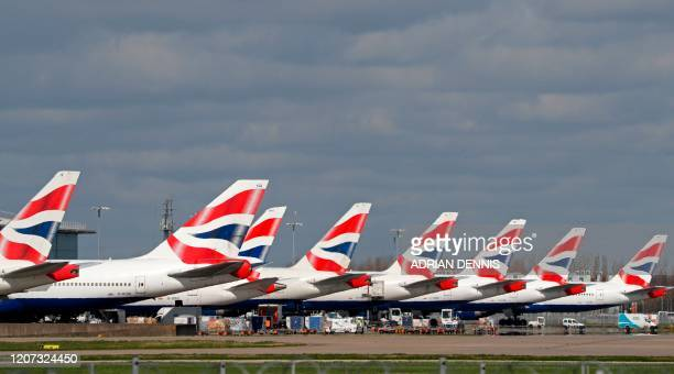 This picture shows British Airways planes grounded at Heathrow's airport terminal 5 in west London on March 16 2020 IAG the owner of British Airways...