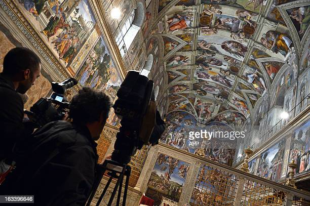 This picture shows cameramen taking views inside the Sistine chapel being prepared for a cardinals conclave on March 9 2013 at the Vatican The...