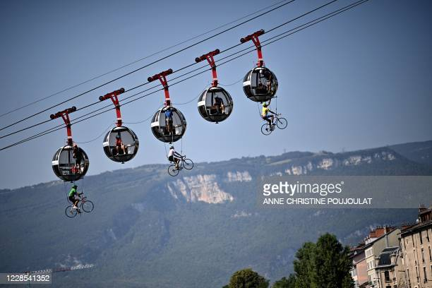 This picture shows cyclists hanging under the Grenoble Bastille cable cars during the 17th stage of the 107th edition of the Tour de France cycling...