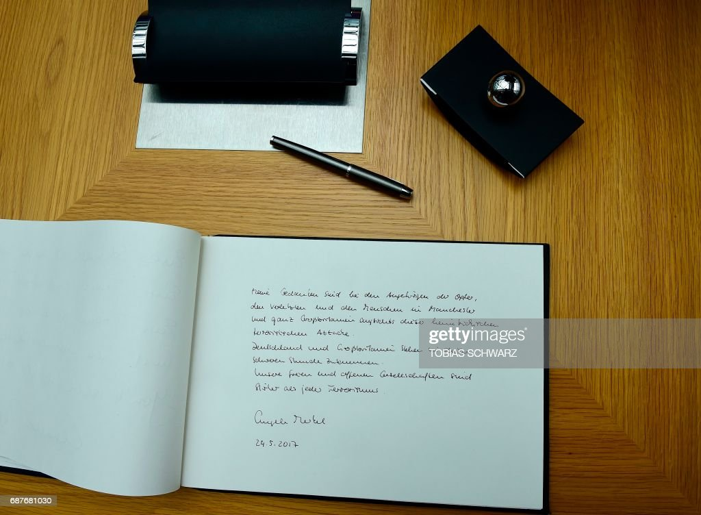 This picture shows German Chancellor Angela Merkel's message in a book of condolence at the British embassy in Berlin, on May 24, 2017, following the terror attack at the Ariana Grande concert at the Manchester Arena in Manchester on May 22. 'My thoughts are with the relatives of the victims, the injured ones, and with the people of Manchester and of all Great Britain, facing this insidious terrorist attack. Germany and Britain stand together in this difficult hour. Our free and open societies are stronger than any terrorism.' Twenty two people have been killed and dozens injured in Britain's deadliest terror attack in over a decade after a suspected suicide bomber targeted fans leaving a concert of US singer Ariana Grande in Manchester. PHOTO / POOL / Tobias SCHWARZ