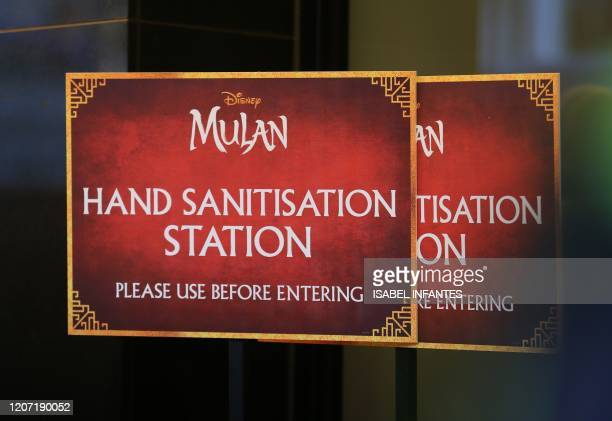 "This picture shows posters asking the customers to use a hand sanitiser before attending a screening of the European Premiere of Disney's ""MULAN"" at..."