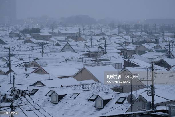 TOPSHOT This picture shows roofs of houses covered with snow in Tokyo on February 2 2018 / AFP PHOTO / Kazuhiro NOGI