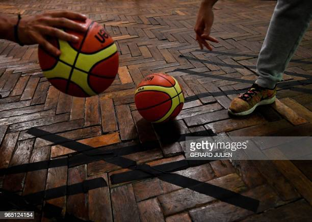 This picture shows temporary repairs to the herringbone parquet as men train in the world's oldest basketball court in Paris on May 31 2018 The court...
