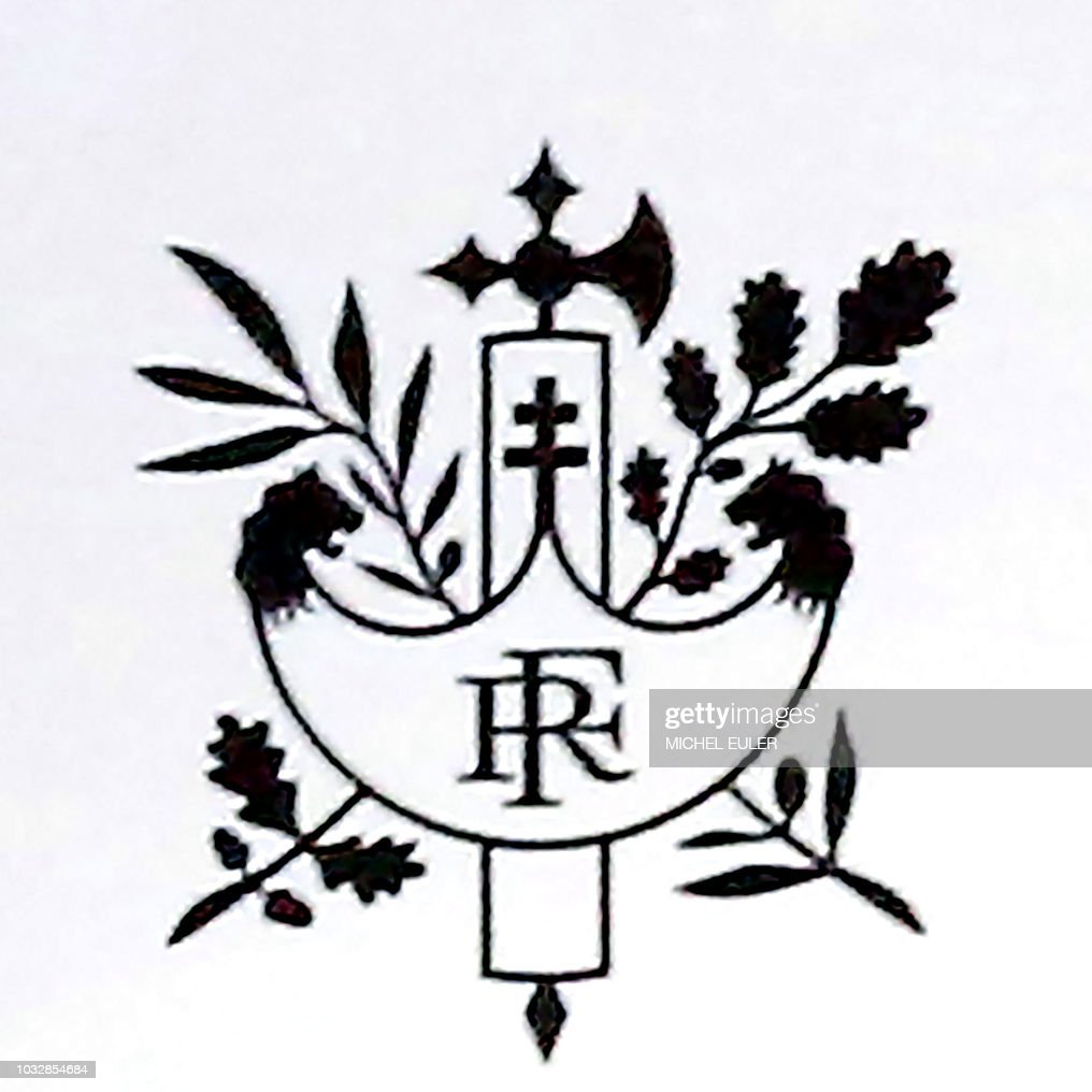This picture shows the detail of one of the French Republic emblems printed on the lectern from which French President Emmanuel Macron addressed a presentation of an anti-poverty plan in Paris on September 13, 2018. - This 'Faisceau de licteur' emblem has been modified by the Elysee Presidential palace with the addition on top of the letter RF (which stand for French Republic) of a Croix de Lorraine, which refers to French former right wing President and wartime leader General Charles De Gaulle.
