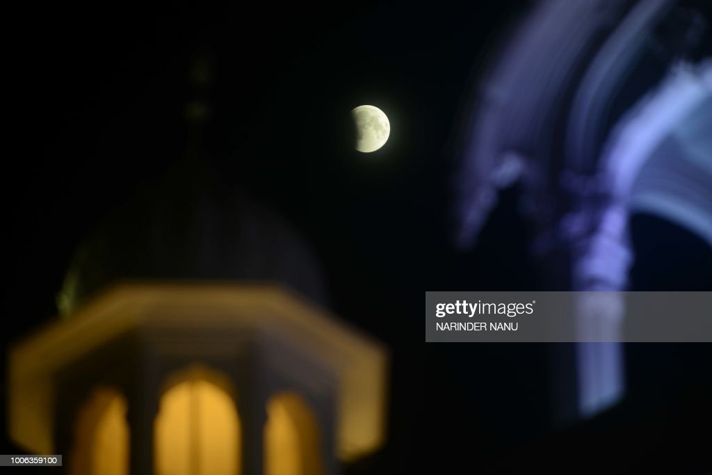 This picture shows the full moon during a `blood moon` eclipse beside the Golden temple in Amritsar early on July 28 2018 The longest `blood moon`...