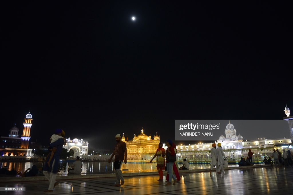 This picture shows the full moon during a `blood moon` eclipse over the Golden temple in Amritsar early on July 28 2018 The longest `blood moon`...