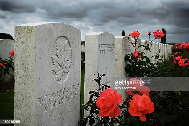 This picture shows the graves of Canadian and Scottish soldiers who perished during World War I. The graves are surrounded by red flowers. Tyne Cot...