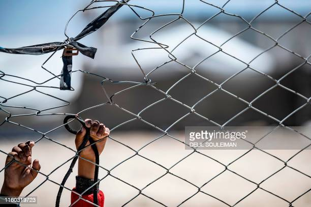 This picture shows the hands of a Syrian child hooked at a fence at the al-Hol camp in al-Hasakeh governorate in northeastern Syria, on August 08,...