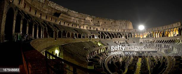 This picture shows the inside of the Colosseum during a preview of the night tour The moon over the colosseum late on May 2 2013 in Rome The moon...