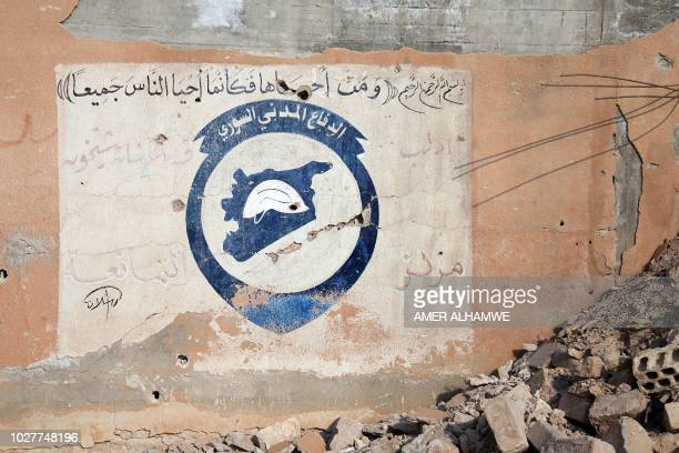 This picture shows the logo of the Syrian civil defence teams known as The White Helmets at one of their centers inside a school after alleged...