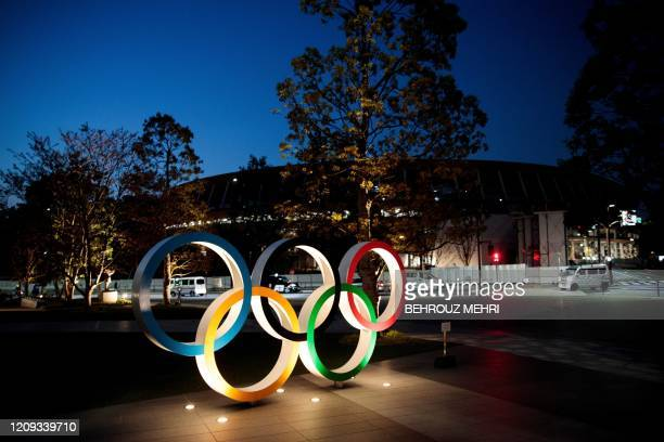 This picture shows the Olympic rings displayed outside the National Stadium a venue for the Tokyo 2020 Olympic Games in Tokyo on April 7 2020 Japan's...