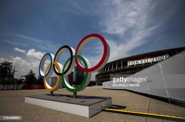 This picture shows the Olympic rings standing in front of the Olympic Stadium in Tokyo on July 20, 2021 ahead of the Tokyo 2020 Olympic Games.