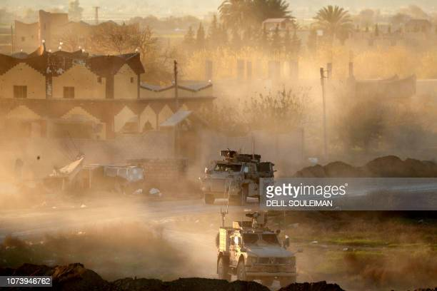 TOPSHOT This picture shows US army vehicles supporting the Syrian Democratic Forces in Hajin in the Deir Ezzor province eastern Syria on December 15...