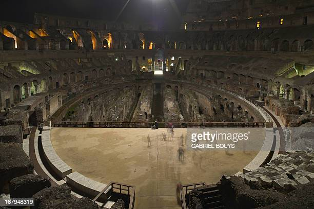This picture shows visitors inside of the Colosseum during a preview of the night tour The moon over the colosseum late on May 2 2013 in Rome The...