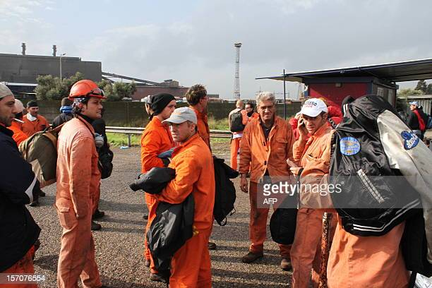 This picture shows workers standing outside the ILVA steel plant in Taranto after it was hit by a tornado on November 28 2012 A worker was missing...