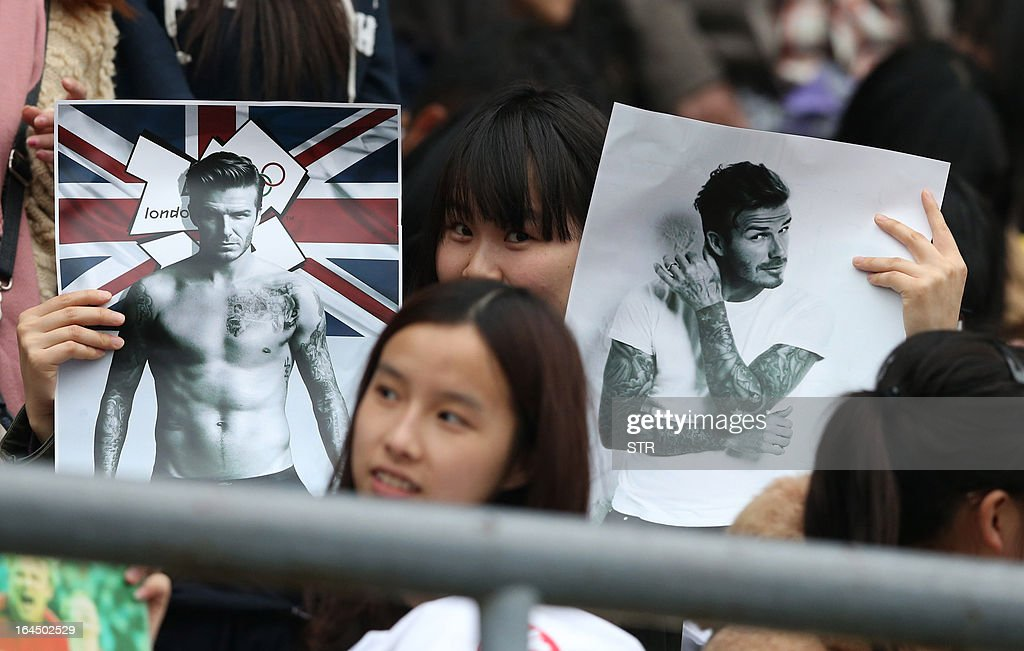 This picture take on March 23, 2013 shows fans holding posters of football superstar David Beckham in a stadium in Wuhan, central China's Wuhan province. Beckham raised the prospect of one last stop on his global football journey on March 20, refusing to rule out playing in China after his contract with Paris Saint-Germain ends. CHINA