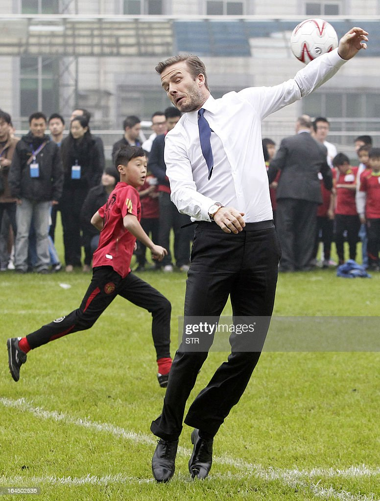 This picture take on March 23, 2013 shows football superstar David Beckham (C) during a game with young players in a stadium in Wuhan, central China's Wuhan province. Beckham raised the prospect of one last stop on his global football journey on March 20, refusing to rule out playing in China after his contract with Paris Saint-Germain ends. CHINA