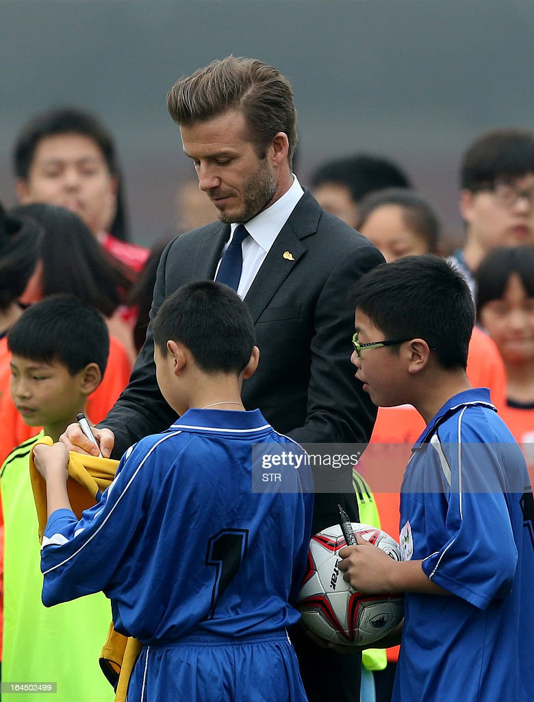 This picture take on March 23, 2013 shows football superstar David Beckham (C) signing autographs during a meeting with young players and fans in a stadium in Wuhan, central China's Wuhan province. Beckham raised the prospect of one last stop on his global football journey on March 20, refusing to rule out playing in China after his contract with Paris Saint-Germain ends. CHINA
