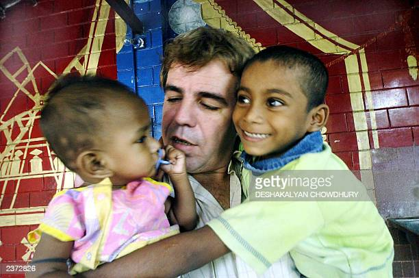 "This picture taken 01 August 2003 shows Thierry Darnaudet, a French social worker and head of the NGO ""New Light"" holding a pair of Indian children..."
