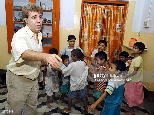 "This picture taken 01 August 2003 shows Thierry Darnaudet, a French social worker and head of the NGO ""New Light"", dancing with a group of Indian..."