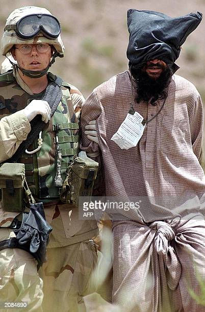This picture taken 02 June 2003 shows an US military officer escorting an Afghan prisoner suspected of being a Taliban part of the Al Qaeda forces...