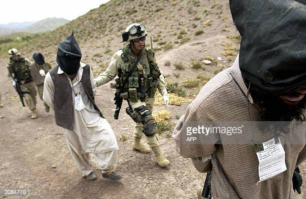 This picture taken 02 June 2003 shows US soldiers of the 82nd Airborne leading Afghan prisoners suspected of being Taliban part of alQaeda forces...
