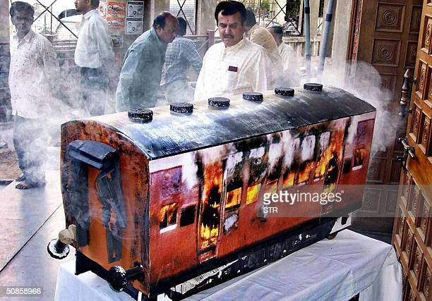 This picture taken 06 December 2002 shows a man looking at the replica of a burning wagon of the Sabarmati Express in the VHP's headquaters in...