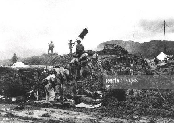 This picture taken 07 May 1954 shows a Vietnamese soldier waving a flag atop a French PC as others assault the area at the Dien Bien Phu battlefield...