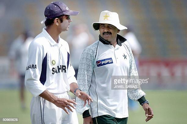 This picture taken 08 April 2004 shows Pakistani cricket team coach Javed Miandad talking with Indian cricketer Rahul Dravid prior the start of a...