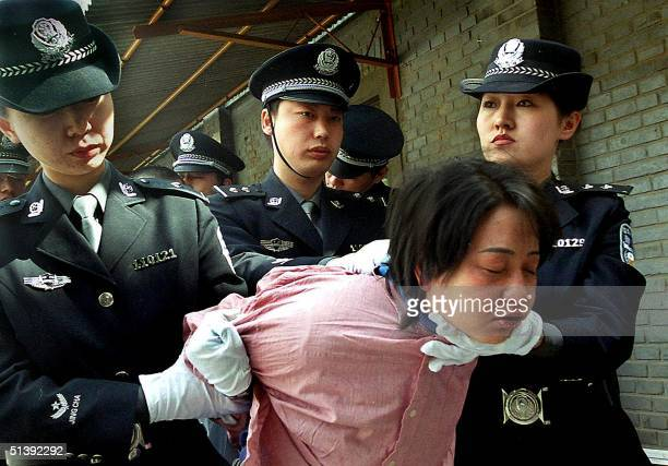 This picture taken 20 April 2001 shows a woman prisoner being taken away for her execution after she was sentenced to death at a sentencing rally in...