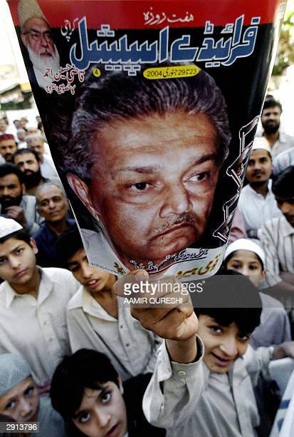 This picture taken 23 January 2004 shows Pakistani youth displaying a magazine with the portrait of Pakistani nuclear scientist Abdul Qadeer Khan...