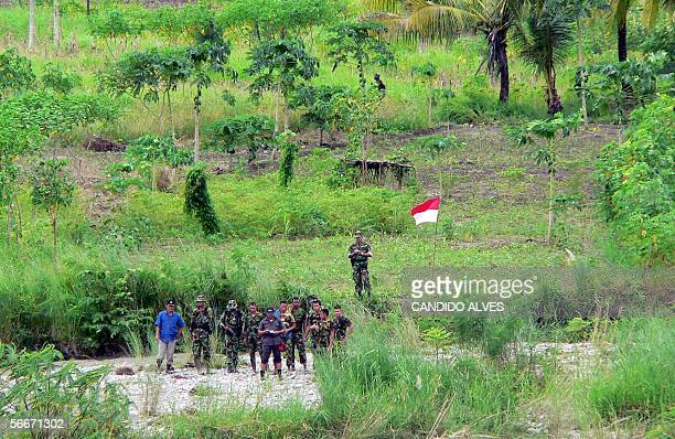 This picture taken 25 January 2006 from Bobonaro border area of East Timor shows Indonesian soldiers watching both countries officials conducting a...