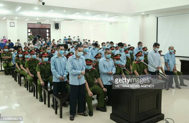 This picture taken and released by the Vietnam News Agency on September 14, 2020 shows defendants involved in a land dispute attending a court trial...