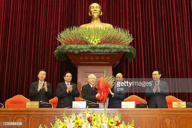 This picture taken and released by the Vietnam News Agency on January 31, 2021 shows Vietnam's Prime Minister Nguyen Xuan Phuc congratulating the new...