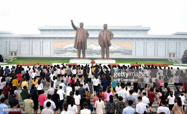 This picture taken and released from North Korea's official Korean Central News Agency on September 9 2017 shows North Korean residents offering...