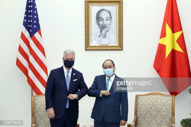 This picture taken and released on November 21, 2020 by the Vietnam News Agency shows Vietnam's Prime Minister Nguyen Xuan Phuc bumping elbows to...