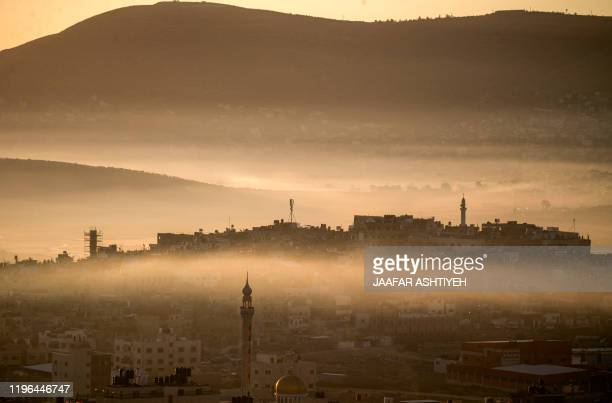 This picture taken around sunrise on January 26, 2020 from Nablus in the occupied West Bank of a general view of its eastern valley shows the Askar...