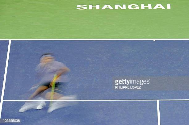 This picture taken at a slow shutter speed shows Roger Federer of Switzerland returning a shot against Novak Djokovic of Serbia during their semi...