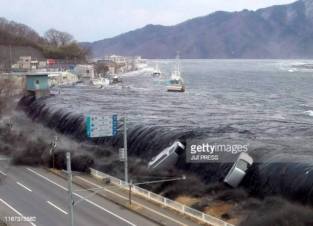 This picture taken by a Miyako City official on March 11, 2011 and released on March 18, 2011 shows a tsunami breeching an embankment and flowing...