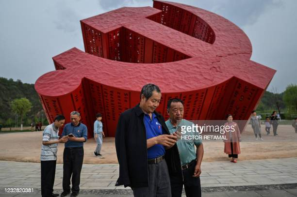 This picture taken during a government organised media tour shows people looking at the photos they took next to a monument of the hammer and sickle...