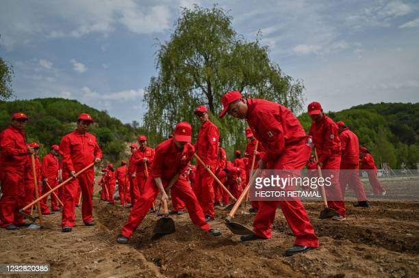 This picture taken during a government organised media tour shows employees from an oil company who came to this rural area to plant pumpkins in...