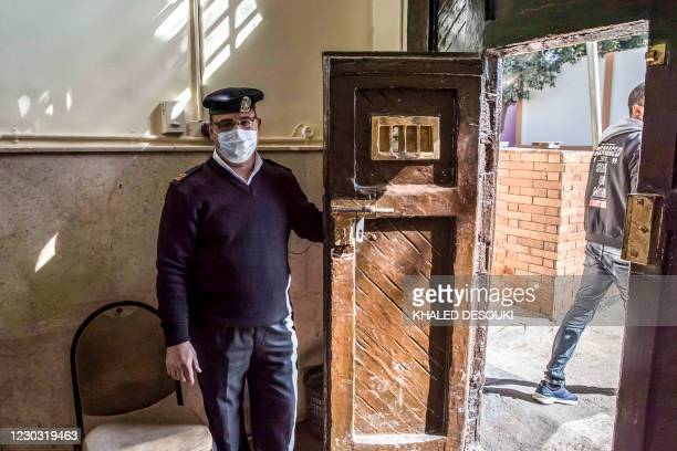 This picture taken during a government-guided tour on December 27, 2020 shows a policeman opening the gate to al-Qanatir women's prison, at the tip...