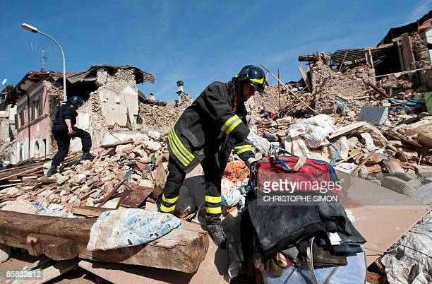 This picture taken during a guided tour with Italian firemen shows a fireman pulling clothes from the remains of a house after a violent earthquake...