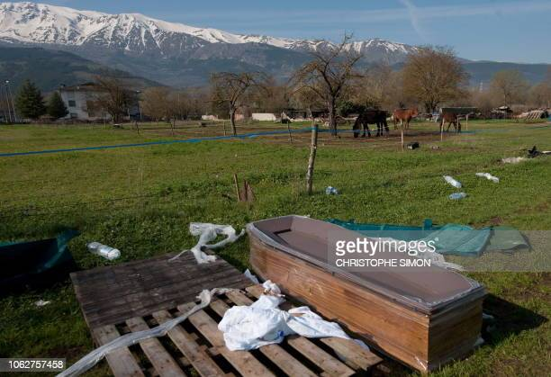 This picture taken during a guided tour with Italian firemen shows an empty coffin in a field after a violent earthquake the day before, on April 7,...