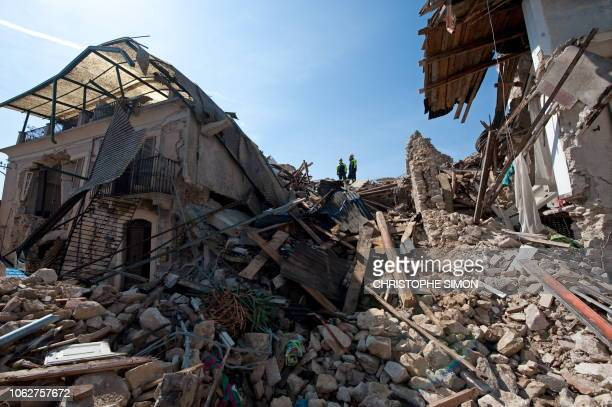 This picture taken during a guided tour with Italian firemen shows rescuers standing on rubble after a violent earthquake the day before, on April 7,...