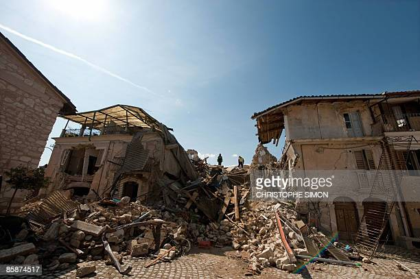 This picture taken during a guided tour with Italian firemen shows rescuers standing on the remains of houses which collapsed after a violent...