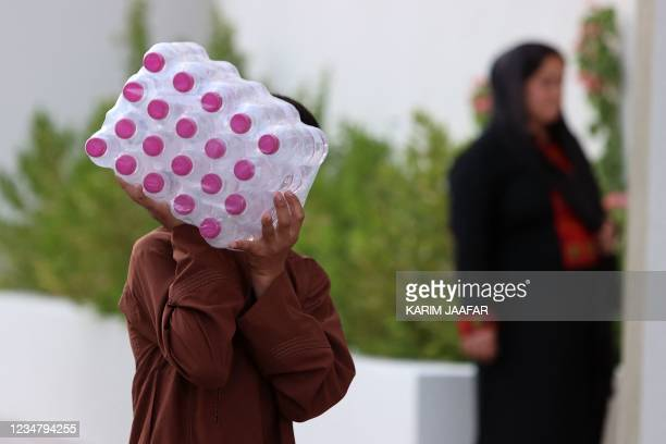 This picture taken during a media visit organised by the Qatari authorities on August 21 shows an Afghan man carrying bottled water inside a villa...