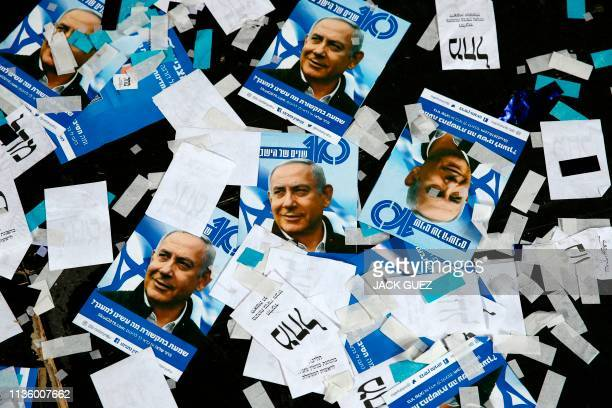 TOPSHOT This picture taken early on April 10 2019 shows Israeli Likud Party campaign material and posters of Prime Minister Benjamin Netanyahu strown...